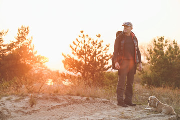 Backpacker and dog in lens flare sunset Wall mural