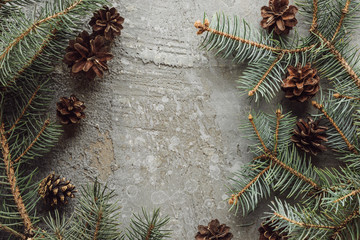 top view of fir branches and dry cones on grey stone surface