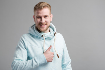 a young man in blue sweater in front of a grey background shows thumb up