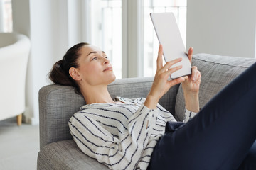 Young cheerful woman relaxing with tablet on sofa