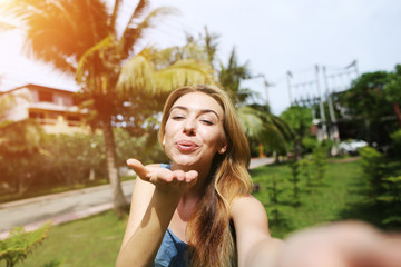 joyful woman send air kiss to comera taking selfie, traveling to sunny Thailand with palms and green grass