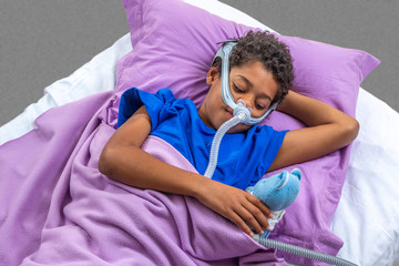 Child suffering from Sleep Apnea, wearing a respiratory mask.