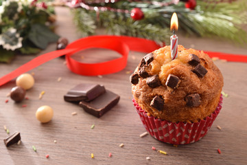 Chocolate muffin with red mold and lit candle elevated