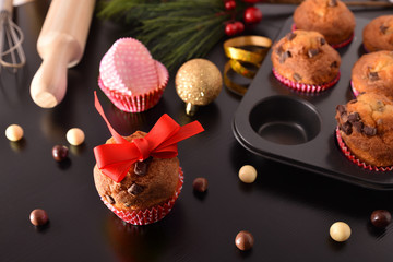 Homemade chocolate muffins for christmas parties on black table elevated