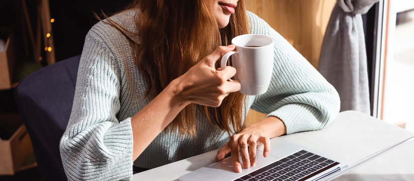 cropped view of woman drinking coffee while using laptop in cafe