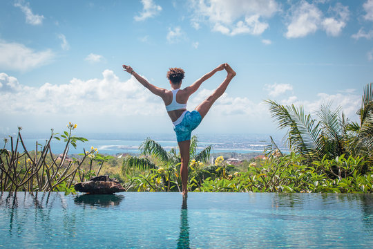 Young woman practicing yoga pose ashtanga hatha asana on the edge of infinity pool with breathtaking view at private villa in Bali