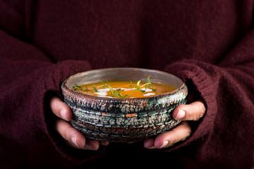 Hands with bowl of orange pumpkin soup. Selective focus.