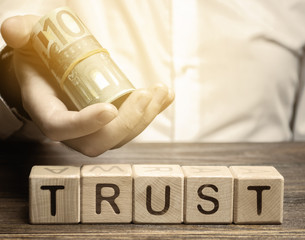 Wooden blocks with the word Trust and money in the hands of a businessman. Trust relationships between business partners, friends, relatives. Respect and authority. Confidence in a person.