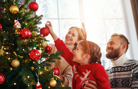happy family mother, father and child daughter decorate Christmas tree  .
