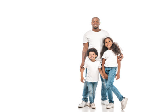 happy african american father, sister and brother smiling at camera on white background