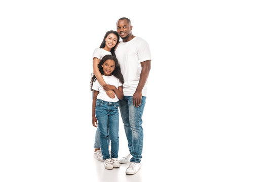 happy african american woman hugging adorable daughter while standing near smiling husband on white background