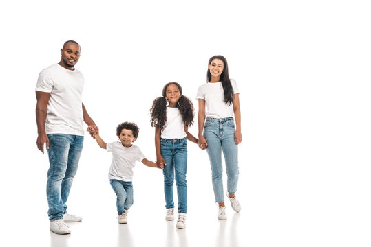 happy african american parents holding hands with daughter and son while standing on white background
