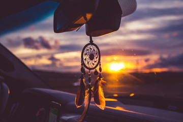 dream catcher on car over blurred highway background.