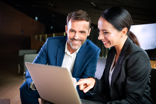 Businesswoman with laptop talking with colleague during meeting