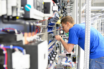 young apprentice assembles components and cables in a factory in a switch cabinet - workplace industry with future