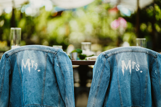 Bridal jeans jackets are hanging on the chairs backs outdoors on the sunny day