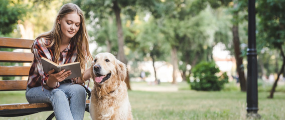 Wall Mural - panoramic shot of beautiful girl in casual clothes reading book and petting golden retriever while sitting on wooden bench