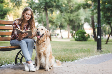 Wall Mural - full length view of beautiful girl in casual clothes reading book and petting golden retriever while sitting on wooden bench