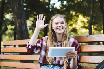 Wall Mural - beautiful girl in casual clothes sitting on wooden bench in park, using digital tablet and waving hand