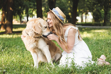 Wall Mural - beautiful young girl in white dress and straw hat feeding golden retriever while smiling and sitting on meadow with closed eyes