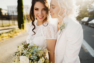 Just married lesbian couple is hugging outdoors and holding big bridal bouquet