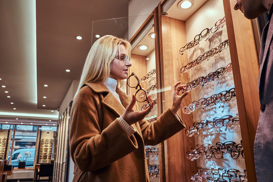 Beautiful young woman is choosing eyeglasses frame in optical store.