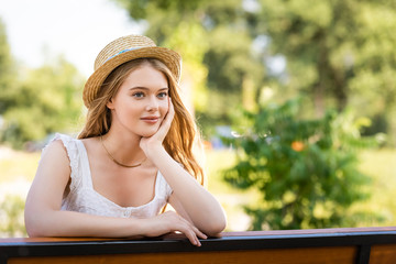 Wall Mural -  beautiful girl in straw hat posing while sitting on bench and looking away