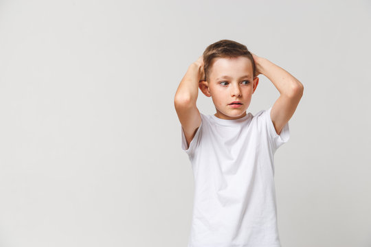 Terrified boy in white t-shirt with both hands on head on gray background