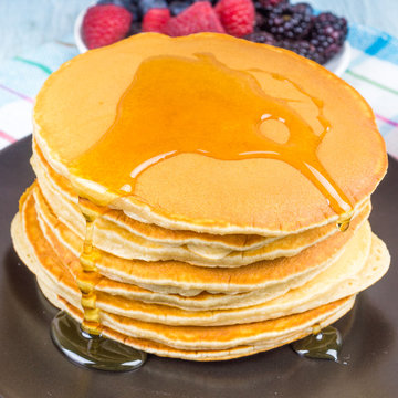 A stack of pancakes with berries and maple syrup close-up on a dark plate