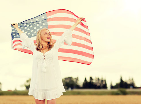 country, patriotism, independence day and people concept - happy smiling young woman in white dress with national american flag on cereal field