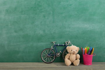 colored crayons and toy bear on the wooden table - elementary school education concept, chalkboard background