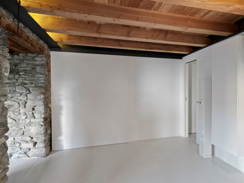 a empty room with wooden ceiling and concrete floor whose walls are of stones