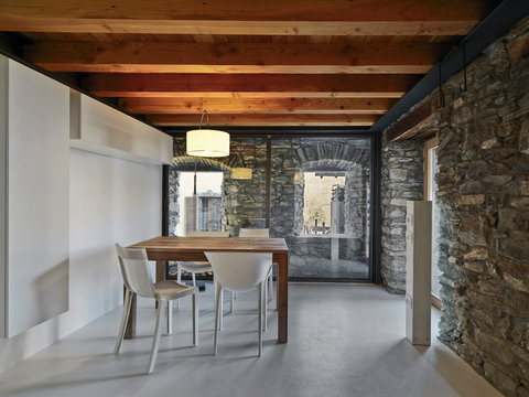 interior view of a dining room with plastic chairs and  wooden table as well as the ceiling,, the walls are made of stones and the floor is made of concrete
