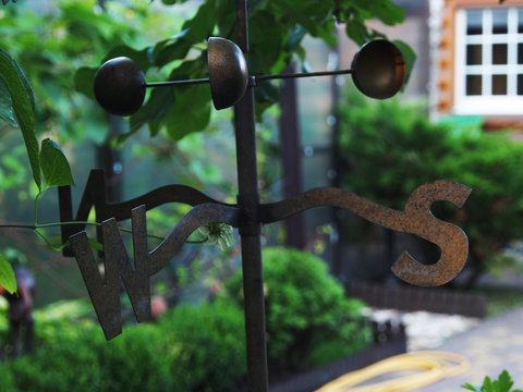 The fragment of the garden weathervanes with pointers sides of the world. Polished metal, close-up of the direction indicator.