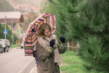 A girl in a scarf under an umbrella in the autumn rain carefully looks at the tree. Concept of autumn and nature in the city.