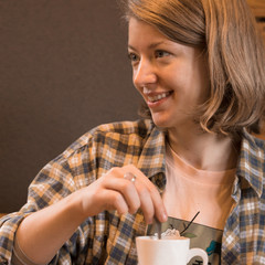 Blonde girl in a plaid shirt at a table in a cafe and a glass teapot.