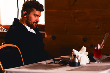 A writer with a beard writes text in a laptop at a table in a cafe.