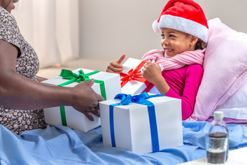 little girl wearing Santa hat receiving her gift while she is in hospital or at home with mother