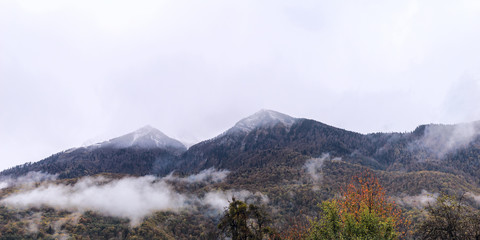 Fog in the mountains against the background of peaks with snow in the fall in Sochi, Russia.