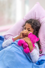 Close portrate cute multiracial girl of 6-10 years old who is sucking his thumb in the bed with pink teddy