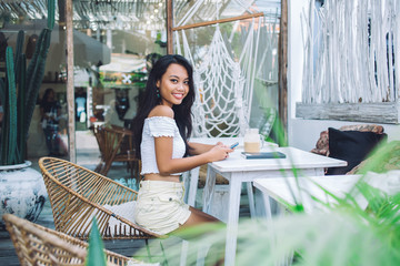 Youthful indonesian woman on terrace outside cafe messaging smiling