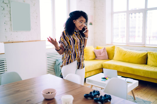 Sad black woman speaking on phone while standing in living room