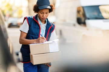 African American deliverer filling document while making delivery in the city.