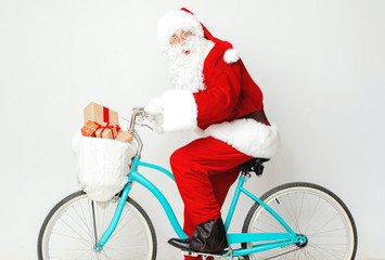 Surprised Santa Claus riding a bike with presents