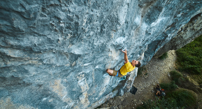 top view of man rock climber in yellow t-shirt, climbing on a cliff, searching, reaching and gripping hold. Conquering, overcoming and active lifestyle concept.