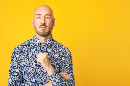 Fabulous at any age. Portrait of 40-year-old man standing over light yellow background in blue shirt. Close up. Hipster style. Bald shaved head. Copy-space. Studio shot