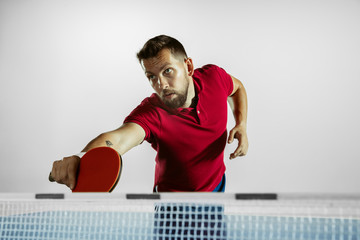 Wall Mural - Goal. Young man plays table tennis on white studio background. Model plays ping pong. Concept of leisure activity, sport, human emotions in gameplay, healthy lifestyle, motion, action, movement.