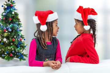 Two Happy little girl in Santa hat, stylish sister, happily looking at each otherto camera while standing near chritsmas tree on white background, profile view