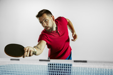 Wall Mural - Strong. Young man plays table tennis on white studio background. Model plays ping pong. Concept of leisure activity, sport, human emotions in gameplay, healthy lifestyle, motion, action, movement.