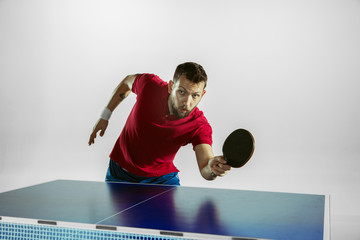 Wall Mural - Time. Young man plays table tennis on white studio background. Model plays ping pong. Concept of leisure activity, sport, human emotions in gameplay, healthy lifestyle, motion, action, movement.